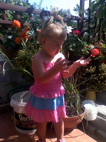 Nicolka zbiera z kwiatków biedroneczki