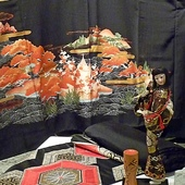 Japońska lalka na tle pięknego męskiego  kimona.