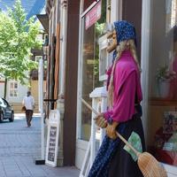 Kobieta z miotłą zachęca do lokalu